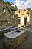 Thermopolium, Herculaneum. Ancient Taberna with storage pots in Scavi Ercolano, Campania, Italy. Thermopolia were Take-away places for the citizens. Portrait Stock Photography