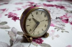 Ancient table clock on tablecloth. Antique table clock on tablecloth with flower pattern Stock Images