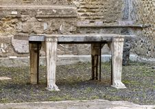 Ancient table in a small room in Parco Archeologico di Ercolano. Pictured is an ancient table in a small room in the Parco Archeologico di Ercolano. The Stock Photo