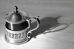 An ancient tea-pot black and white with his shadow stock photo