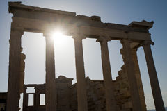Ancient temple. Closeup portico of ancient Greek temple on sky and rays of sun background, Athens Acropolis, Greece Royalty Free Stock Image
