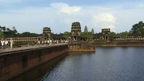 Angkor ancient temple in Cambodia as people walk to it stock footage