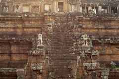 Ancient temple in Angkor Wat. Phimeanakas stair with stone statue in sunset light. Buddhist or hindu temple.
