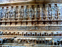 Ancient Temple Carvings. Idols of Gods and Goddesses in different poses carved in yellow sandstone wall of a temple in Rajasthan, India Stock Image