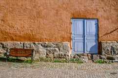 An ancient textured wall with a stone basement, a blue door and a bench. Stock Image