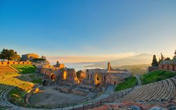 Ancient theatre of Taormina with Etna erupting volcano at sunset royalty free stock image