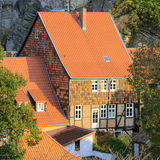 Ancient timber house; Quedlinburg, Germany. Ancient timber house under an orange tiled roof nesting on a steep slope below Quedlinburg Castle; Quedlinburg, Saxen Stock Images
