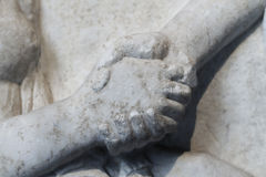 Ancient time deal. Close up of a handshake over an antique stone figure (circa BC 500 Royalty Free Stock Photos