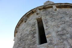 Ancient tiny small church detail. Ancient tiny small white church  against blue sky. Little church made of limestone close up. Small square window hole serves Stock Photos