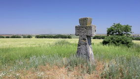 Ancient tomb cross in the green field stock video footage