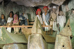 Ancient tombs in cave guarded by puppets. Tana Toraja - Ancient cave tomb. The cave is guarded by a balcony of puppets. Inside the cave is a colection of coffins stock image