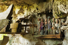 Ancient tombs in cave guarded by puppets. Tana Toraja - Ancient cave tomb. The cave is guarded by a balcony of puppets. Inside the cave is a colection of coffins stock photography
