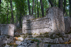 Ancient tombstones in the woods. Karaite Cemetery Balta-Tijmez at Chufut-Kale, the Crimea Royalty Free Stock Photography