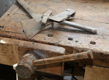Ancient tools small axe and big hammer on the old wooden workben. Ch with a vise Stock Image