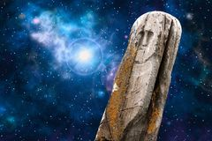 Ancient totem universe. Ancient stone ritual idol totem with a universe image - space, stars, nebula, supernova explosion - as a background Royalty Free Stock Photos