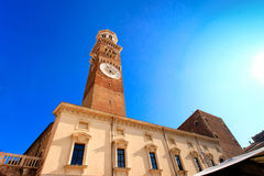 Ancient tower with clock on a blue sky background Royalty Free Stock Photo