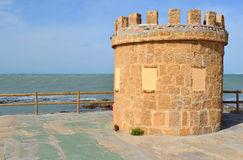 Ancient tower and fence on beach Stock Photography