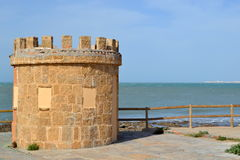 Ancient tower and fence on beach Stock Photos