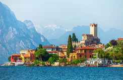 Ancient tower in malcesine old town. Ancient tower and fortress in old town malcesine at garda lake veneto region italy high snowbound top mountains on royalty free stock photo