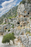 Ancient town Demre in Turkey. Ancient stone town Demre in Antalya Turkey curved in rocks sorrounded byt plants and blue sky above Royalty Free Stock Photography