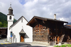 The ancient traditional chalet and Church along the Furkastrasse. Munster Stock Photo