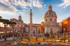 Ancient Trajan Forum at sunset, Rome, Italy. Ancient ruins of Trajan Forum, Trajan Column and churches Santa Maria di Loreto and Most Holy Name of Mary at the Stock Image