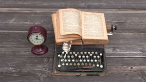 Ancient typewriter and old book on wooden background stock footage