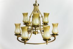 Ancient victorian time chandelier hanging from a ceiling during a masquerade. Chandelier golden color with beige plafonds stock images
