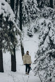 Ancient viking hunter walking in snow winter forest with steel a Stock Photography