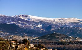 Ancient Village in France in the snow near Aix en Provence. Stone village in France near Aix en Provence with a snowy mountain backdrop Royalty Free Stock Photo