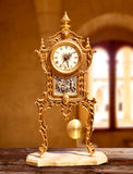 Ancient vintage golden brass pendulum clock Royalty Free Stock Photography