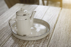 Ancient vintage metal teapot and bottom plate on a corner of wooden table,fitered vintage style,light effect added Stock Images