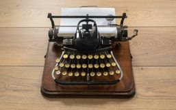 Ancient vintage portable typewriter with non qwerty keyboard. Old vintage portable typewriter with non qwerty type keys on wooden desk royalty free stock image