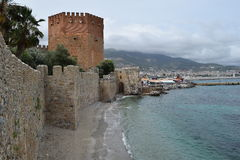 Ancient wall in Alanya and Red Tower, Turkey. Ancient stone wall of Alanya fort in Turkey coast after reconstruction. In background is Red Tower, famous symbol stock photo