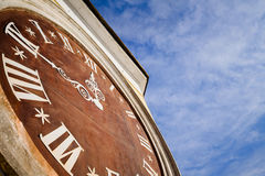 Ancient wall clock. Ancient clock on building wall against blue sky Stock Photo