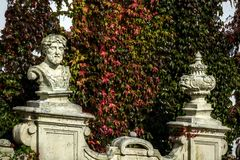 An ancient wall decorated with statuary and covered with colorful ivy around the chateau. In southern Moravia Royalty Free Stock Photography
