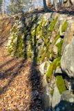 An ancient wall made of moss-covered stones alongside a small forest path royalty free stock photography