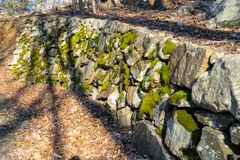An ancient wall made of moss-covered stones alongside a small forest path stock image