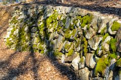 An ancient wall made of moss-covered stones alongside a small forest path stock photography