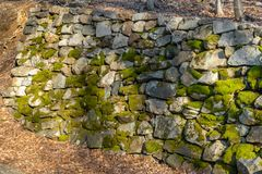 An ancient wall made of moss-covered stones alongside a small forest path stock images