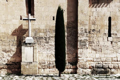 Ancient wall, with a tree and a marble cross Royalty Free Stock Photos