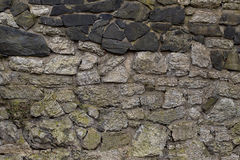 Ancient walls built of gray and black stone base natural background Stock Photo