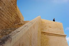 Ancient walls of Citadel, Victoria, Malta. Victoria, Gozo - March 8 2017: Ancient walls of Citadel built of limestone with long stairway. The tourist admires Stock Photos