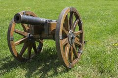 Ancient war cannon. With wooden wheals on green grass|military Royalty Free Stock Photography