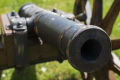 Ancient war cannon. With wooden wheals on green grass|military stock photography