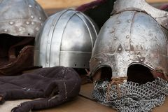 Ancient warrior helmets. Ancient medieval warrior helmets made from iron placed on wooden table Royalty Free Stock Image