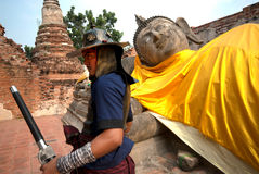 Ancient warrior posing front of Reclining Buddha. Stock Photos