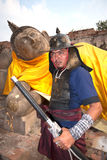 Ancient warrior posing front of Reclining Buddha. Royalty Free Stock Photography