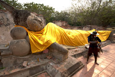 Ancient warrior posing front of Reclining Buddha. Royalty Free Stock Photo