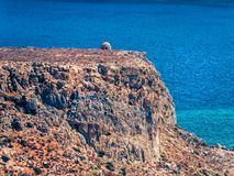 Ancient watchtower atop the rocky hill, surrounded by deep blue sea royalty free stock photo